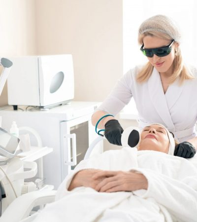 Young beautician in protective goggles using laser device while doing skin tightening procedure to mature woman in beauty salon